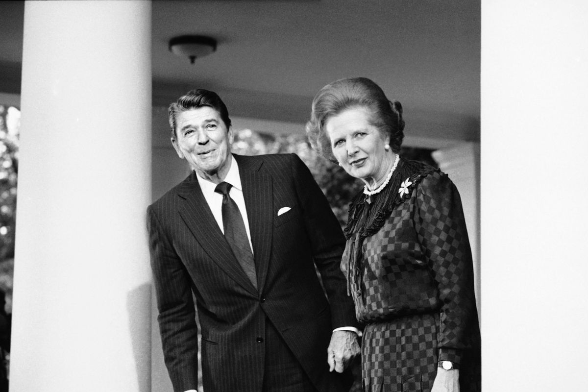 Black and white photo of Ronald Reagan and Margaret Thatcher just outside the White House.