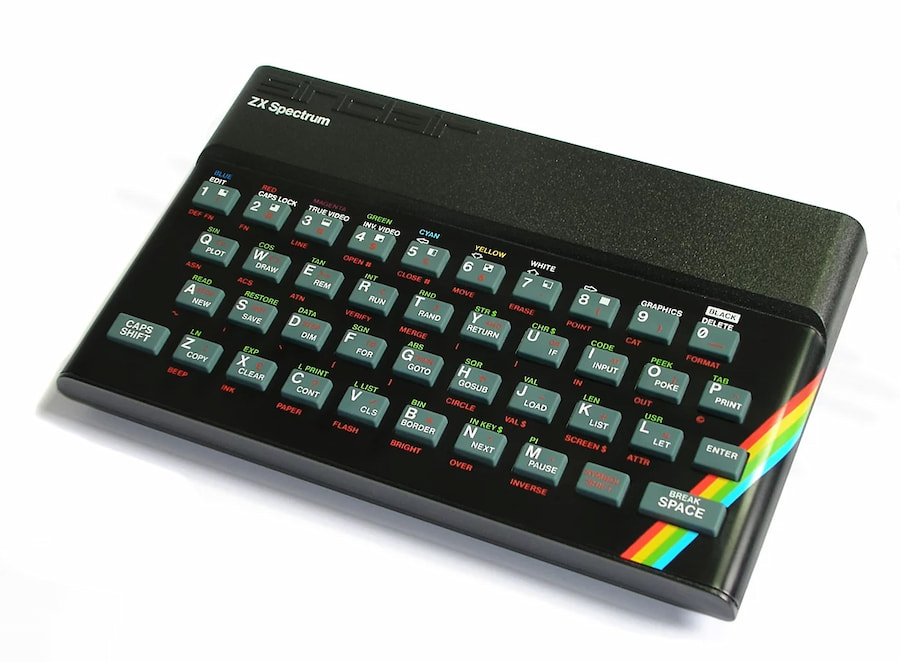 Picture of a ZX Spectrum – black plastic box with rubber keys and a bright rainbow stripe across the bottom.
